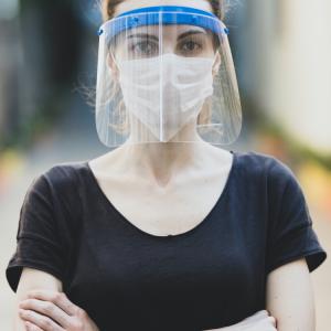Femme, avec masque et plexiglass, barrant la route