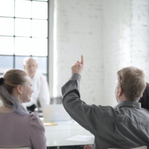 Employé levant la main dans une équipe de travail