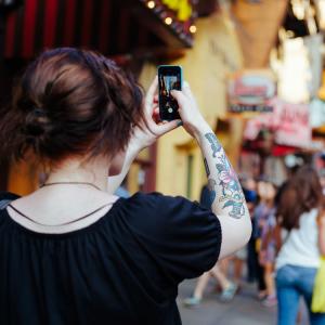 Jeune femme photographiant une rue agitée